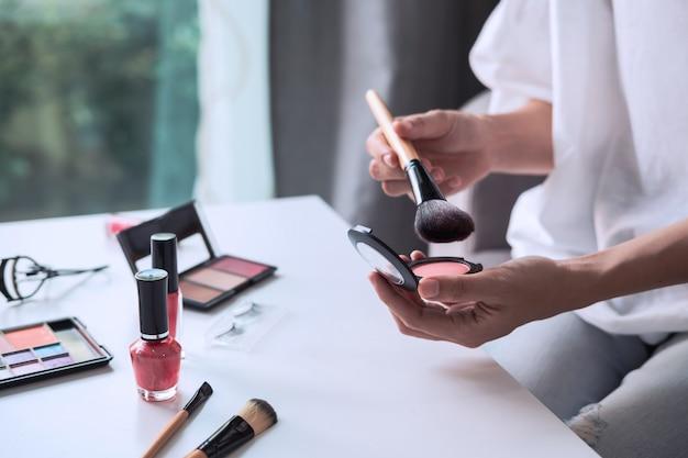 Jovem mulher sentada no sofá e fazendo maquiagem em casa Foto Premium