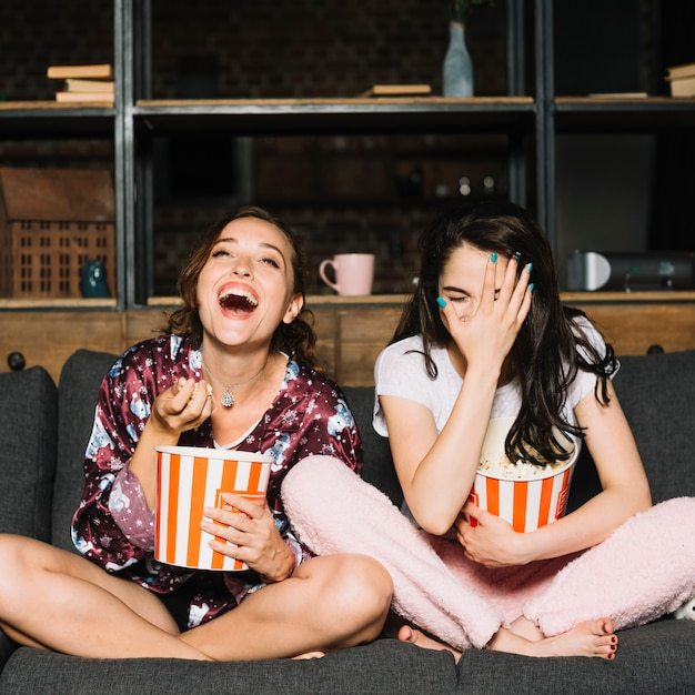 Jovem mulher sentada no sofá rindo enquanto assistia filme Foto gratuita