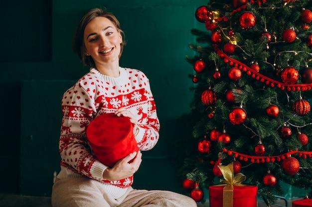 Jovem mulher sentada perto da árvore de natal com caixas vermelhas Foto gratuita