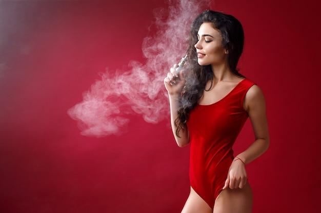 Jovem mulher sexy é vaping. uma nuvem de vapor. fotografia de estúdio. Foto Premium