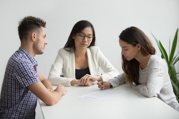 Jovem, mulher, sinal, divórcio, papeis, em, advogado, escritório Foto gratuita