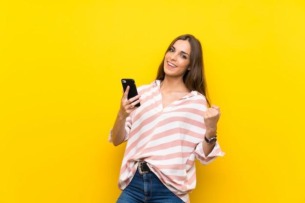 Jovem mulher sobre fundo amarelo isolado com telefone em posição de vitória Foto Premium