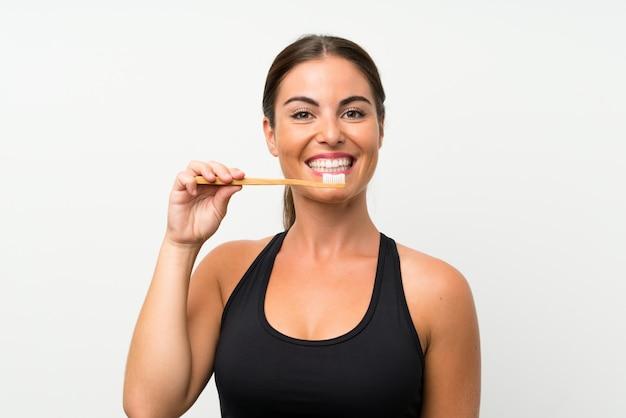 Jovem mulher sobre parede branca isolada, escovando os dentes Foto Premium