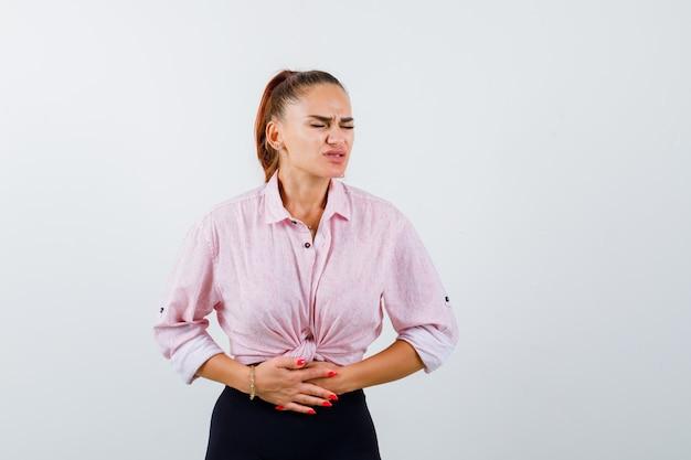 Jovem mulher sofrendo de dor de estômago em uma camisa casual, calças e parecendo doente. vista frontal. Foto gratuita