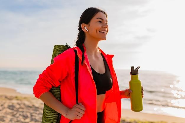 Jovem mulher sorridente atraente praticando esportes no nascer do sol da manhã na praia do mar segurando um tapete de ioga e uma garrafa de água, estilo de vida saudável, ouvindo música em fones de ouvido e vestindo uma jaqueta corta-vento rosa Foto gratuita