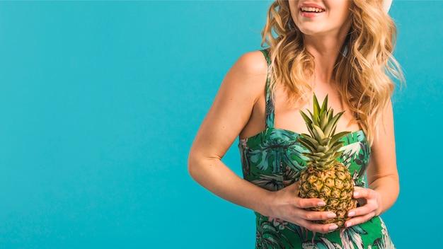 Jovem, mulher sorridente, em, flowered, vestido, segurando, abacaxi Foto gratuita