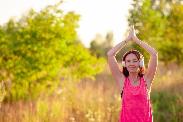 Jovem mulher sorridente fazendo exercícios desportivos ao ar livre Foto Premium