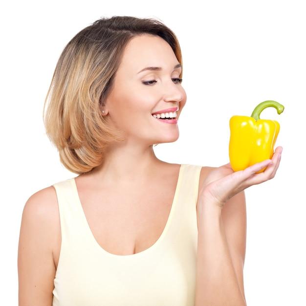 Jovem mulher sorridente saudável contém pimenta isolada no branco. Foto gratuita