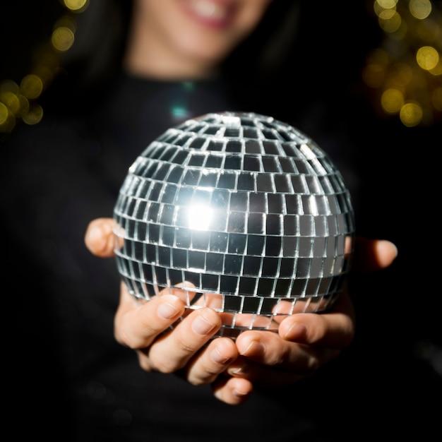Jovem mulher sorridente segurando bola de discoteca Foto gratuita