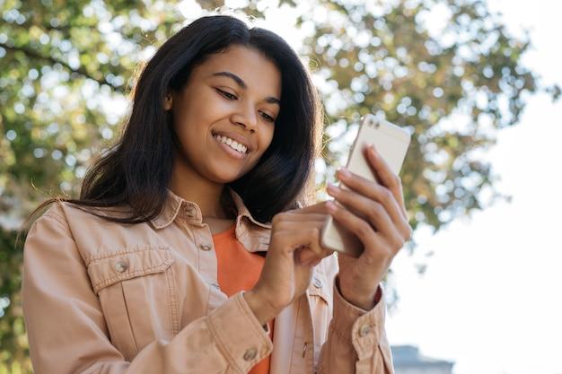 Jovem mulher sorridente segurando smartphone, conversando, comunicação, olhando para a tela digital Foto Premium