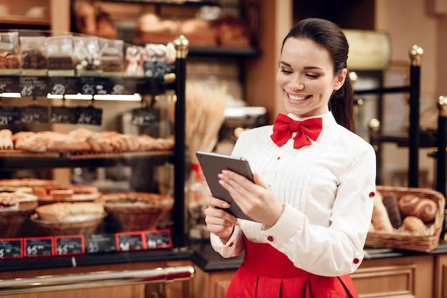 Jovem mulher sorridente usando tablet na padaria moderna Foto Premium