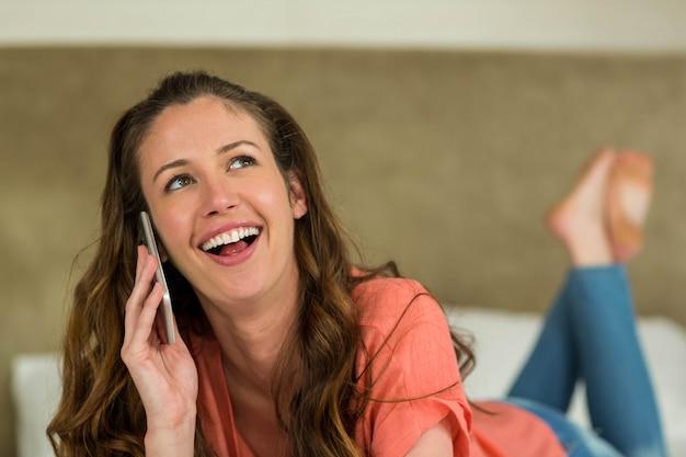 Jovem mulher sorrindo e falando no telefone enquanto estava deitado na cama Foto Premium