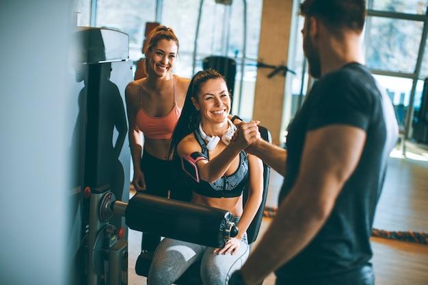 Jovem mulher tendo exercícios na extensão da perna e máquina de enrolar as pernas no ginásio Foto Premium