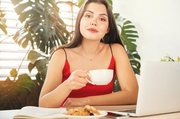 Jovem mulher tendo uma pausa para café enquanto está sentado em seu escritório Foto Premium