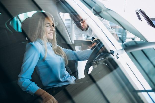Jovem mulher testando um carro em uma sala de exposições Foto gratuita