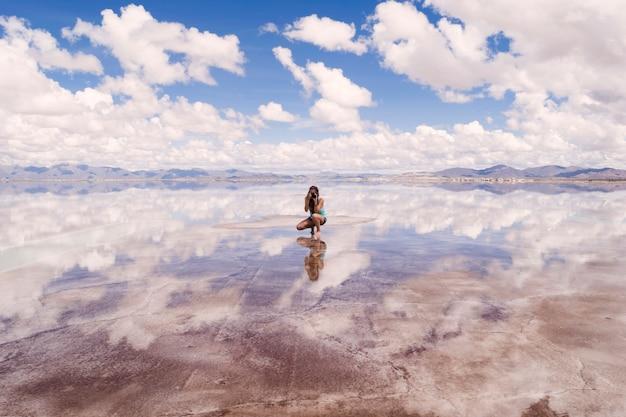 Jovem mulher tirando foto de reflexo de água bonita Foto gratuita