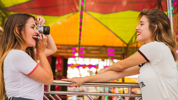 Jovem mulher tirando foto do seu amigo sorridente no parque de diversões Foto gratuita
