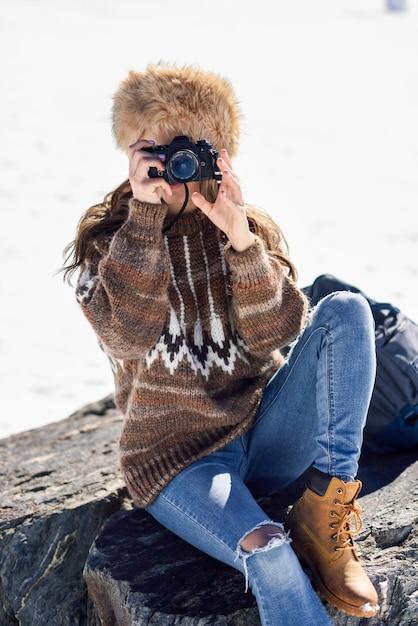 Jovem mulher tirando fotos nas montanhas nevadas Foto Premium