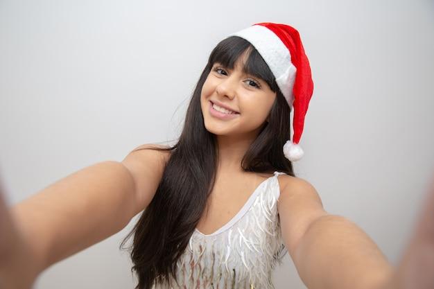 Jovem mulher tirando selfie com chapéu de papai noel Foto Premium