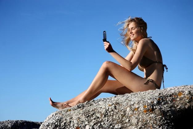 Jovem mulher tirando uma foto com o celular em uma rocha do mar Foto Premium