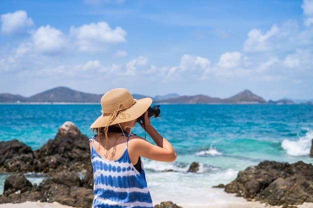 Jovem, mulher tirar uma foto na praia tropical Foto Premium