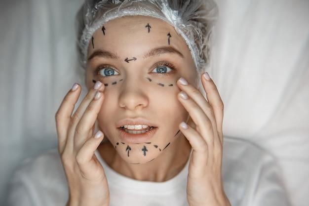 Jovem mulher tocando seu rosto e olhar. ela tem marcas na pele. modelo concentrado. Foto Premium