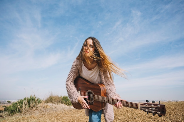 Jovem, mulher, tocando, violão, natureza Foto gratuita