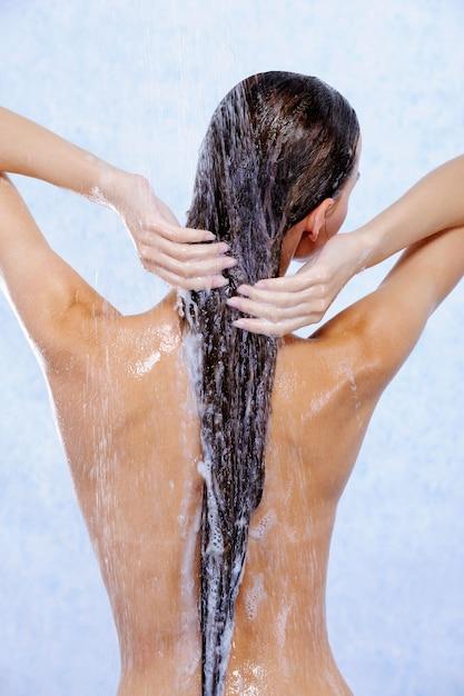 Jovem mulher tomando banho e lavando o cabelo - vista traseira Foto gratuita