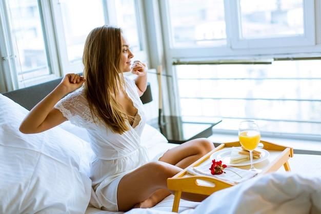 Jovem mulher tomando café da manhã na cama no quarto Foto Premium