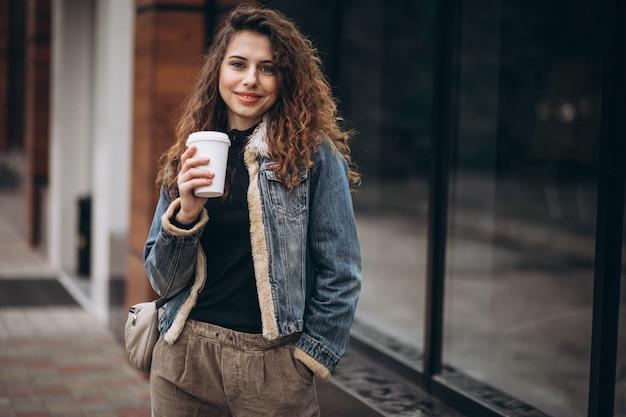 Jovem mulher tomando café e usando o telefone Foto gratuita