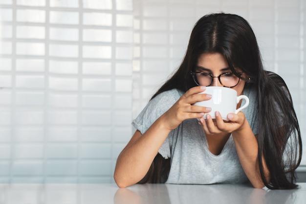 Jovem mulher tomando café em casa Foto Premium