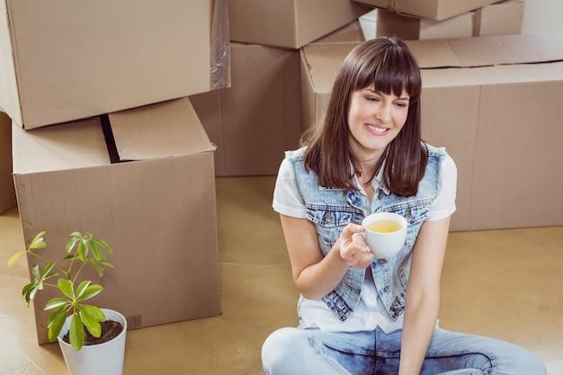 Jovem mulher tomando café em sua nova casa Foto Premium