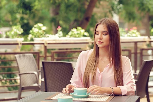Jovem mulher tomando café em um café ao ar livre Foto Premium