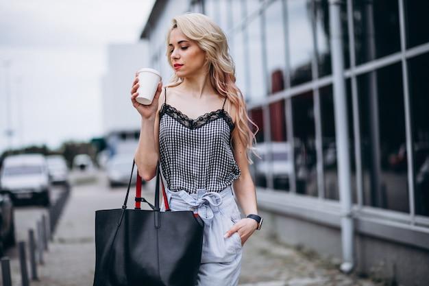 Jovem mulher tomando café fora da rua Foto gratuita