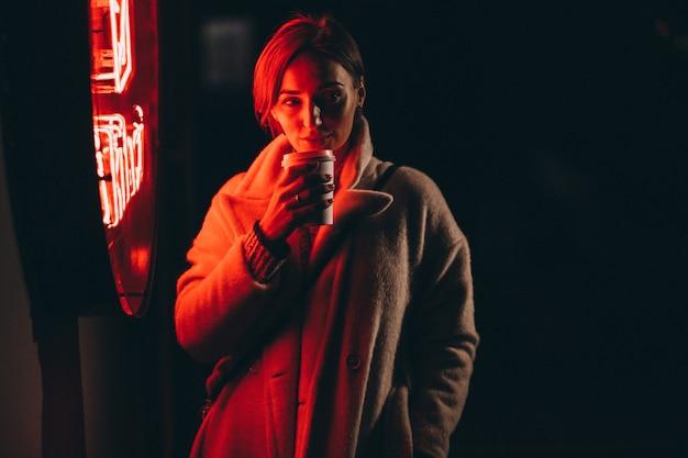 Jovem mulher tomando café na rua à noite Foto gratuita