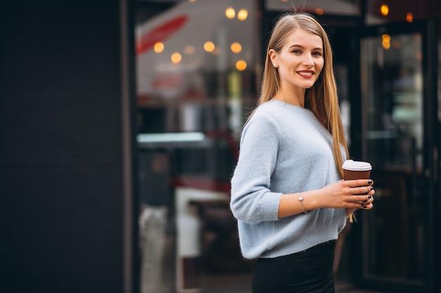 Jovem mulher tomando café no café Foto gratuita
