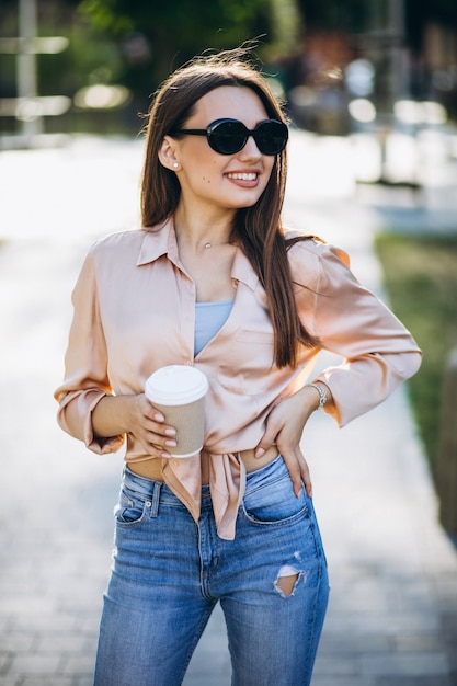 Jovem mulher tomando café no parque Foto gratuita