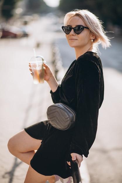Jovem mulher tomando café para sair da rua Foto gratuita