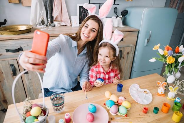 Jovem mulher tomando selfie com a filha perto de ovos de páscoa Foto gratuita