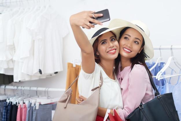 Jovem mulher tomando selfie com amigo Foto gratuita