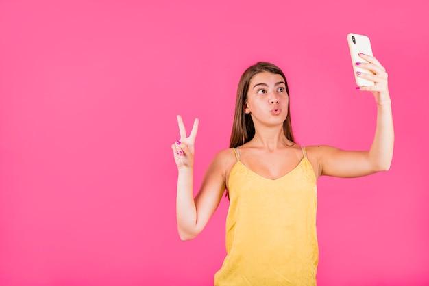 Jovem mulher tomando selfie em fundo rosa Foto gratuita