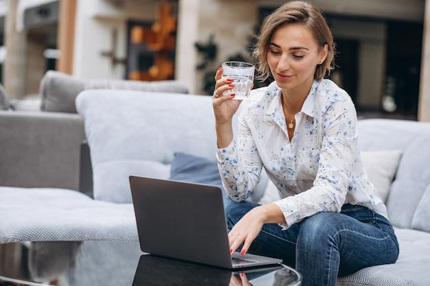 Jovem mulher trabalhando em um computador em casa Foto gratuita