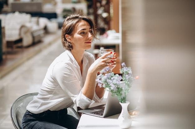 Jovem mulher trabalhando em um computador na cozinha Foto gratuita