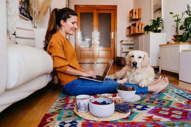 Jovem mulher trabalhando no laptop em casa. cão bonito retriever dourado além disso. Foto Premium