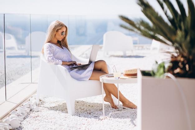 Jovem mulher trabalhando no laptop em um período de férias Foto gratuita