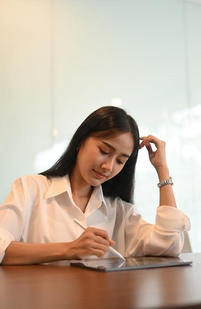 Jovem mulher usando a caneta stylus, planejando seu projeto no tablet digital em um escritório mínimo. Foto Premium