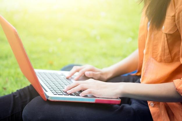 Jovem, mulher, usando computador em óculos verdes no parque. Foto gratuita