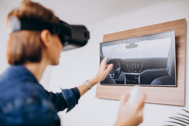 Jovem mulher usando óculos vr e jogando jogo virtual usando o controle remoto Foto gratuita