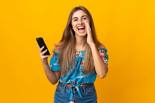 Jovem mulher usando telefone celular sobre parede amarela gritando com a boca aberta Foto Premium