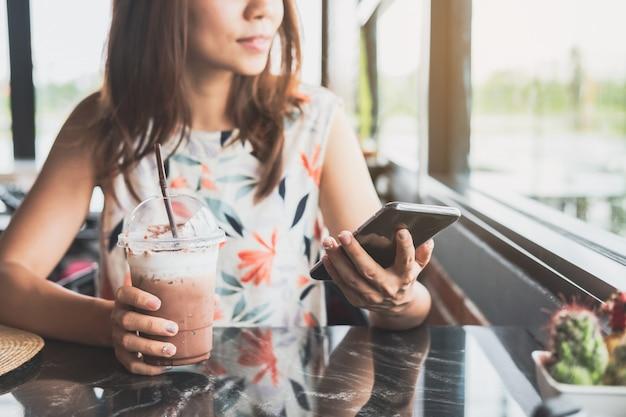 Jovem mulher usando telefone inteligente com bebidas no café Foto Premium